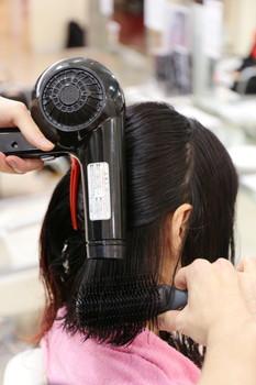 内側の髪からブラシですくって、ドライヤーの風がブラシの上部にあたるように乾かす