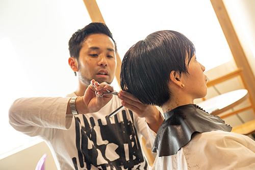 荒井さんの髪をカットする永井さん